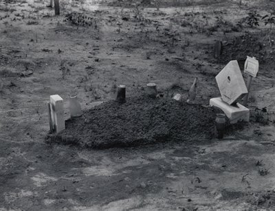 grave with mounded soil; bottles and jars on top of grave; four markers--two at each end; bare soil with some scrubby plants