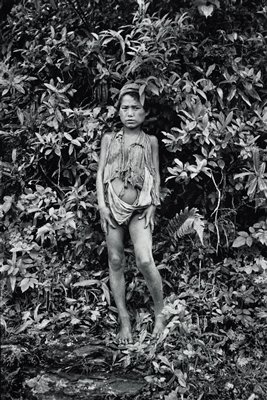 child with dirty legs standing in front of dense foliage; child wears ragged and torn shirt, and loin cloth and cap