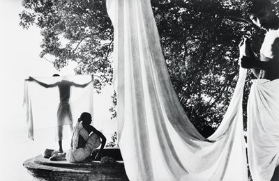 man at R with a sheet wrapped around his waist, holding the end of another draped sheet at center of image; two other men at L: one standing, holding a sheet behind his back, the other seated; tree in background