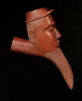 red stone; carved in the shape of a man's face, wearing a cap, with long squared-off beard and moustache