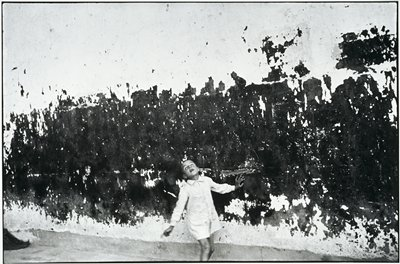 child looking up with hand on a paint pealed wall