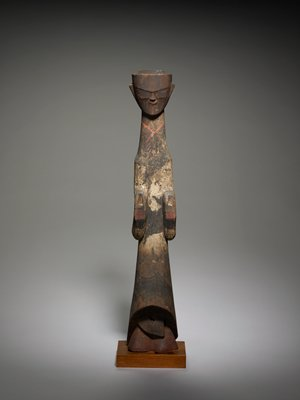 very tall, elongated figure; triangular-shaped face; very close-set features; painted eyes and garment details in red, black and white; long sleeves; mostly dark brown patina overall
