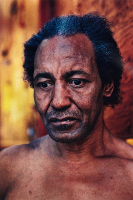 bust of black man, bare chest; yellow/ orange backdrop