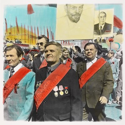 people marching--some wearing red sashes with Russian text--with four men in suits in foreground; two men at left wear medals on their jackets; red banners in background at left; two large yellow placards--one with portrait of Lenin, the other with the portrait of a man wearing many medals