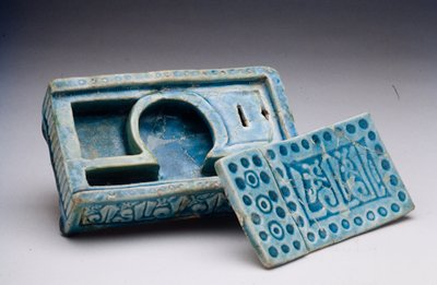 Inkstand, turquoise blue glaze. Ornamentation of Cufic inscription. Cover. Earthenware with turquoise blue glaze over molded decor.