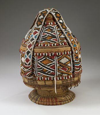 Basket woven with plant fiber and heavily beaded with black, white, orange, blue and red beads. Flared stem base with cone-shaped lid. Two straps cross over the top and are secured at sides.