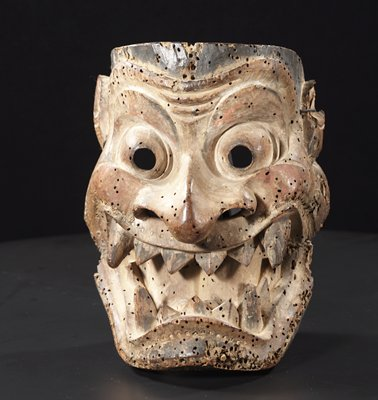 carved wooden mask with large, bulging eyes, huge nose with flared nostrils, wide open mouth exposing pointed teeth and curved tongue; high cheekbones; arched eyebrows; traces of white, red, and black pigment