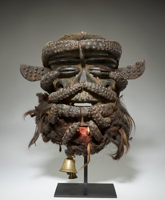 heavy face mask with six pairs of tusk-like elements extending across face; very wide nose; open cylindrical shaped element on each cheek; coffee bean shaped eyes; pair of protruding animal-like ears; mouth has a pair of lower protruding fangs with red pigment inside mouth; beard of hair and fur; three metal bells hang from chin; dark patina; studded overall with brass nailheads
