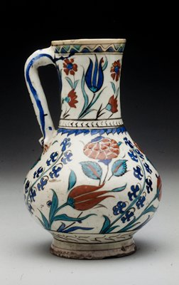Pitcher; with straight handle; white glaze with floral design in dark blue turquoise blue and tomato red with watery black outlines; tulip, open rose and wild hyacinth; so called Rhodian ware.