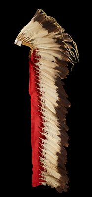 headdress with leather cap/headpiece with beaded band around front top with white beads with two lines of blue triangles, two red bars and two lines of red and orange triangles at either end; long red wool strips at each side of headdress, backed with buffalo hide; brown and cream eagle feathers overall; some feathers at top have light brown horsehair strands attached to ends; eagle feather at center back accented with bright red and bright purple feathers; images of cows' heads drawn on leather beneath feathers on crown of head
