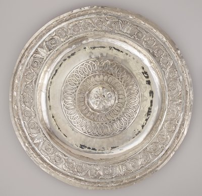 large, thin, round silver platter; central three-dimensional applied large flower form with five petals and cluster of six round elements at center; three round patterned bands around central flower (from interior outward): zigzagging ribbon around central circle, row of feathers or leaves, intertwined football shapes on stippled ground; outer rim has wide band of scrolls, flowers and foliage; outer raised band with looped motif around a round core