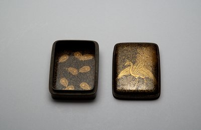 square box with rounded corners; black lacquer with gold flecks; stylized peacock with outstretched wings and erect tail on cover; peacock feather designs in gold inside