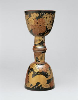 drum core in shape of two adjoined chalices; black lacquer with gold flecked grape vines, leaves, and squirrels