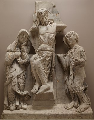 "Romanesque relief-carved stone Calvary group showing Christ on the cross between standing figures of the Virgin Mary on the left and St. John the Evangelist on the right; Christ appears with a perizonium around his waist, his legs buckling to the left and his head raised but with heavy eyelids; Mary's hair is covered by a simple veil which encloses her left elbow and is held in her right hand, looking down, with her left hand raised to her face; Mary's mantle clings to her legs in a series of ""damp fold"" drapery swirls, and ruffles over her pointed shoes; John holds a book in the crook of his left arm, and with his right hand (fingers now missing) gestures up towards the body of Christ; John's bare feet protrude from under a long garment with a crinkled neckline; just visible above the surviving section of the patibulum of the cross are two small, rounded shapes that most likely formed the tips of a wing, presumably of an angel; five metal pins at top of lower portion for secure installation of heads of John and Mary and torso and head of Christ"