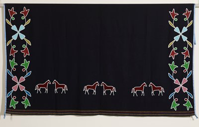blue wool with red, white and yellow stripes at long sides; edged with blue ribbon at short sides; floral beadwork at short sides; three pairs of beaded red horses edged in white along bottom
