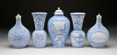 oval concave base; sides flare outward slightly from base then steeply inward about halfway up body of vessel, then slightly outward again along tall neck to wide oval mouth opening; white porcelain with light blue designs; decorated on one side with an Asian garden with a large rock at right, arcing bridge with two figures left of center and two buildings at bottom and butterflies and flowers at top; opposite side decorated in Asian style with three figures on a balcony overlooking water with a figure on a raft and large bird with flowers, bats and waves at top; decorative bands with flowers and patterns at top, bottom and shoulder