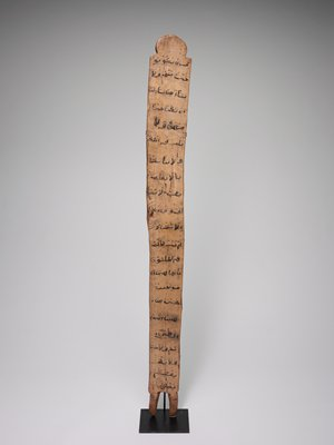 tall, narrow wooden board with two-pronged base, rounded, carved top; widely spaced, horizontal lines of writing on each side of board