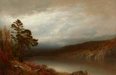 landscape with lake in foreground with brown mountains on opposite shore; tall snow-covered mountain peaks in background with low clouds; trees and bushes, including one bush with red leaves, at left
