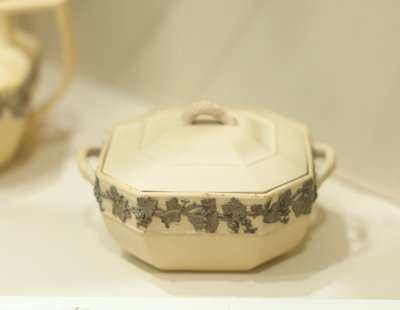 Covered sugar bowl, buff colored cane ware with band of grapevine design in relief, octagonal shape, ceramic, English, XIXc cat. card dims 3 x 4-1/2 x 5-1/2'; needs to be renumbered (says 'a' and 'g')