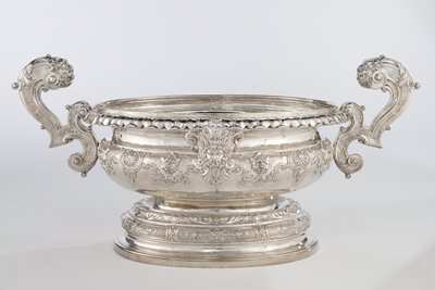 the oval bowl of the wine cooler rests on a similarly shaped foot comprised of a plain concave molding and a vertical base rim surmounted by a convex repoussé band; rim and bowl are linked in the center of either lone side of the oval bowl by a large cash male head surrounded by exhuborant scrolls and moldings Weight: 703 troy ounces = 48 lbs. and 3.29 oz.
