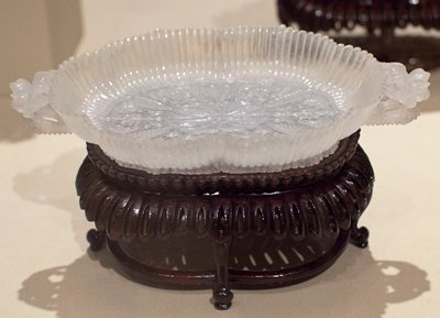 Dish, oval, in the form of a formalized medallion within a fluted border of chrysanthemum petals; two undercut floral handles; medallion boss carved with floral and foliate designs radiating from a central floral form. Translucent camphor jade with flocculent crystalline markings. One of a pair- 36.7.5-6. Former Classification: Jade