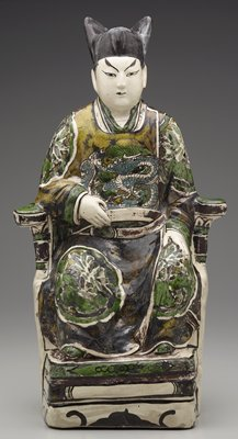 male figure seated on a chair placed on a small podium; man has PL hand on thigh and PR hand on belt; glazed in green, blue, brown and yellow; dragon on front of man's garment