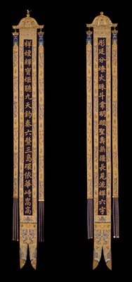 One of a pair of Imperial prayer banners in imperial yellow k'ossu made up of one wide and two narrow strips attached to a gilded bronze plaque with two dragon heads. The central strip, terminating in slit shaped ends finished with wedge-shaped plaques of gilded bronze, is formed of blue-black k'ossu with an inscription in gold characters mounted in yellow k'ossu, which has a design of the Eternal Sea, slender, five-clawed dragons, bats, and clouds in shades of blue, green, violet, crimson, and pink. The side strips suspended from shaped gilt bronze plaques incised with scrollscarry the same dragon and cloud design and terminate in three narrow strips of blue k'ossu with meander fret in gold. The strips are attached to the yellow band by three gilt bronze fungus heads, which are repeated on ends of blue strips. Lining of egg-shell silk of medallion design. These banners are said to have flanked the Emperor's private alter in the Temple of the Forbidden City. Of superb quality and condition. See Harris label for translation of inscriptions.
