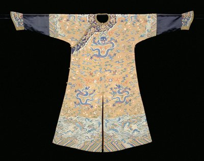 Imperial robe of gold k'ossu with nine five-clawed dragons in blue. In the ground, loosely drawn clouds, the eight Taoist emblems, the bat, flowering branches with peach and couble peach, peonies and narcissus in shades of blue, red, rose, green, peach, yellow, mauve, and brown. Border with narrow band of slanting wavy stripes below tossing wave. Note that the sacred mountain, as well as certain other parts of border, has been painted. Same border treatment at elbows, where sleeves continue with a section of black satin and are finished with an inferior quality of dark blue k'ossu with dragons, clouds, bats, etc. Edging of black and gold brocade; same k'ossu collar and band. Coat slit back and front; lined with thin, gold colored damask. K'ossu broken at shoulders and on collar.