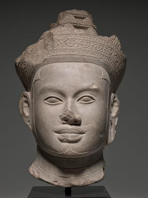 Head from an image of a diefied king carved in sandstone wearing a very elaborate crown and a diadem tied with a knot at the back of his head. Crisply delineated facial features carved in high and low relief. Original encrusted patina. First Angkor style, style of Koh Ker, Cambodia.