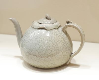 covered wine ewer melon-shaped with curved spout and handle simulating bamboo; motif of peonies, lotus flowers and vines; grey-green celadon glaze and cream underglaze; porcelaneous ware with incised decor under celadon glaze
