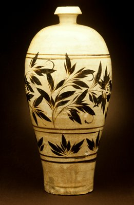 Tzu Chou Vase, tall slender form with wide shoulders rounding to a small nozzle-shaped mouth, boldly painted in iron-brown over white slip with a broad frieze of peony spray between double line borders and with freely brushed leaf clusters in glaze ending unevenly around the foot, the base unglazed revealing the hard gray stoneware.