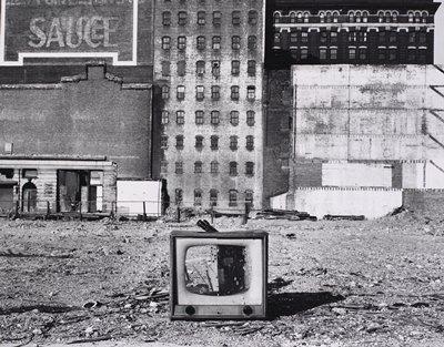 Empty TV cabinet in foreground of rubble, derelict buildings in background