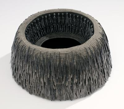 grey bowl form made of rings of looped fibers; darker grey interior and bottom; dark iron wire standing male figures around inner rim; exterior decorated with drip-shaped iron drops hooked between woven fibers