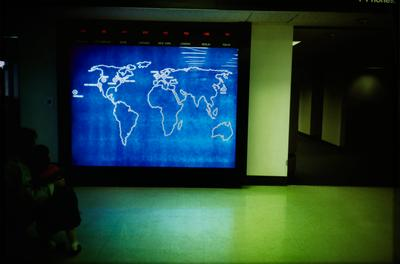 adult and small child squat on the floor at LL as they look at a large, blue screen with a world map in a green-tinted airport hallway; current times of eight different cities around the world are shown above map