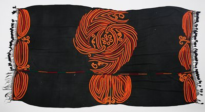 black ground fabric; embroidered in predominately orange with some red and yellow highlights; central leaf- or feather-like motifs with floral and leaf forms; scrolling leaves or feathers at each end; band of red, orange and green off-center; black netting trim at short ends with black tassels