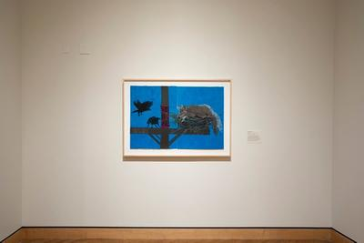 bright blue paper diptych; image of a coyote laying in a nest on a telephone pole in silhouette; two black birds on the L side of image; framed in blonde wood