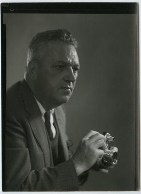 Black and white photograph of a man wearing a suit holding a camera and looking to the viewer's right; image cropped below his forearms