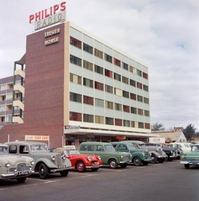 "Color photograph of the exterior of a building with cars parked in front of it; sign on building says ""Philips Radio"""