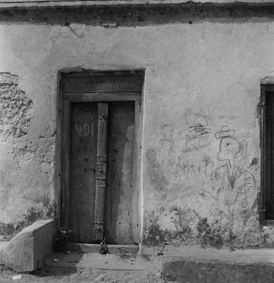 Black and white image of a doorway with 491 on it; graffiti on the wall to the right