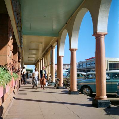 Color image of two woman walking down a outdoor promenade with arches along the right side