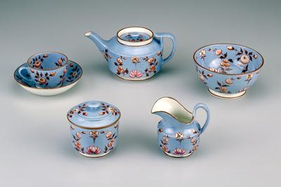 light blue with brown stems, leaves and rims; flowers have been hand painted; crafted in light weight pottery; teapot cover is recessed with a steam hole in the center of the finial; cream pitcher has a wide lip; sugar bowl fits over the base; waste bowl is large