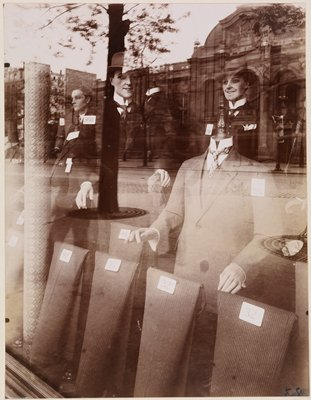 reflections of street in a store window. The window has mannequins dressed in suits and hats and lengths of fabric.