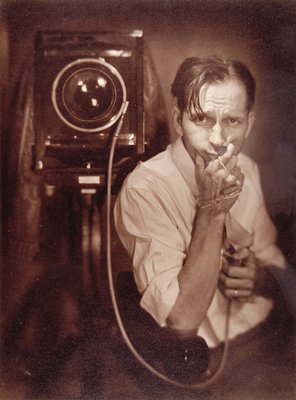 man holding glasses next to large format view camera