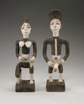 bi-colored black and white female figure with explicit sexual attributes; seated (partially kneeling) on square base; very light wood