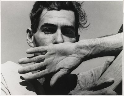 head and shoulders of a man with dark hair, with his PL hand, palm out, over his mouth