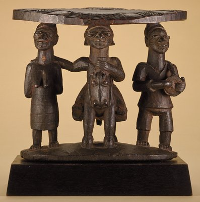 Three figures as a support for a round top. PL figure is holding drum, center figure is on a horse and PR is female with a child on her back. Figures on irregularly shaped base.