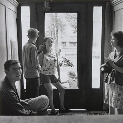 four teenagers inside an apartment building entry: seated boy at LLC, boy and girl leaning against door, girl in plaid skirt at right