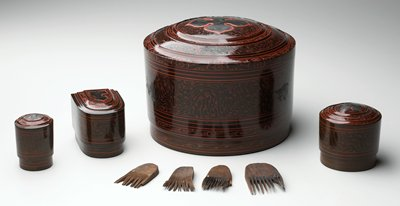 cylindrical box with stepped cover; inlaid flower on cover; organic and geometric patterns overall in red and brown; rouge residue inside container