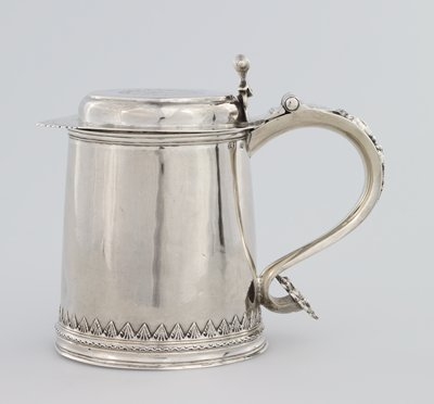 tankard; flat engraved top serrated in front; corkscrew thumb piece; body decorated near base with foliate border; handle decorated with cherub motif; embossed handle tip