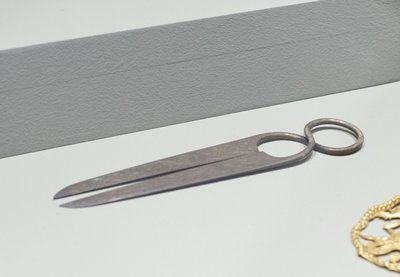 pair of shears, the tapering blades joined through a figure-of-eight-shaped spring-handle and decorated on each side with a bird in flight and scrolling foliage, on a ground of ring-matting